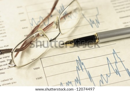 Financial charts pen and glasses. - stock photo