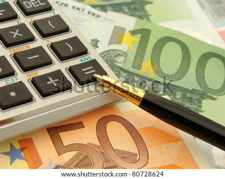 Financial concept - close-up of pen and calculator with money notes in the background