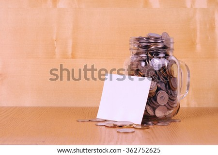 Financial concept. Coins in glass money jar on wooden background - stock photo
