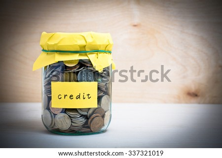 Financial concept. Coins in glass money jar with credit label. Wooden background - stock photo