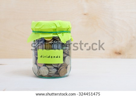 Financial concept. Coins in glass money jar with dividends label. Wooden background - stock photo