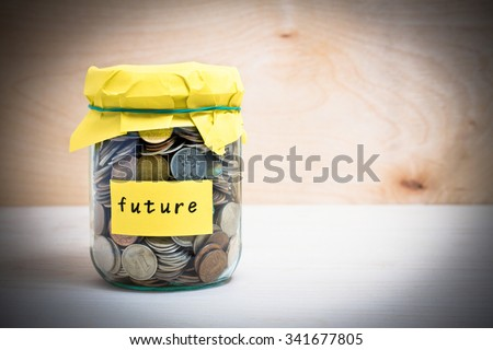 Financial concept. Coins in glass money jar with future label. Wooden background - stock photo