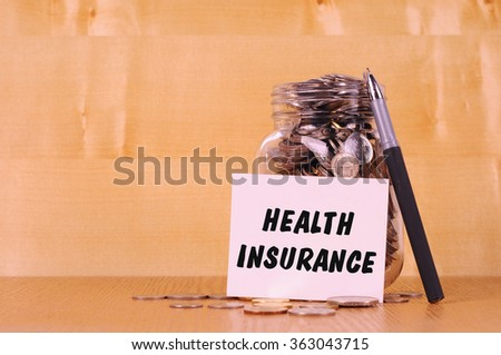 Financial concept. Coins in glass money jar with health insurance label. Wooden background - stock photo