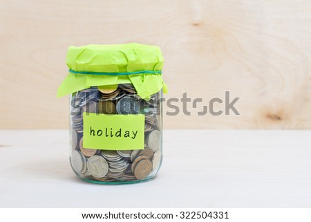 Financial concept. Coins in glass money jar with holiday label. Wooden background - stock photo