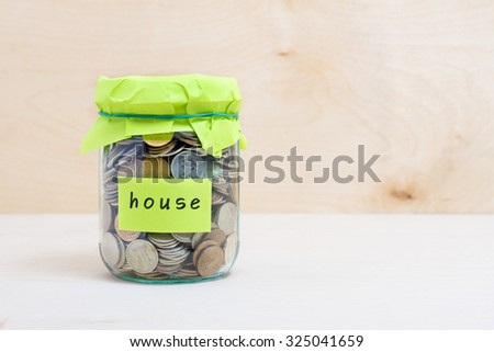 Financial concept. Coins in glass money jar with house label. Wooden background - stock photo