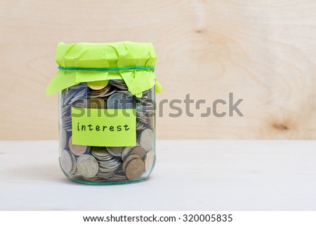 Financial concept. Coins in glass money jar with interest label. Wooden background - stock photo