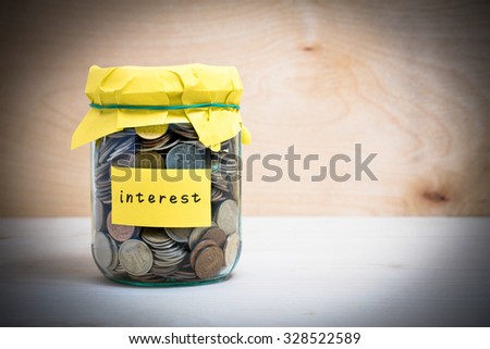 Financial concept. Coins in glass money jar with interest label. Wooden background