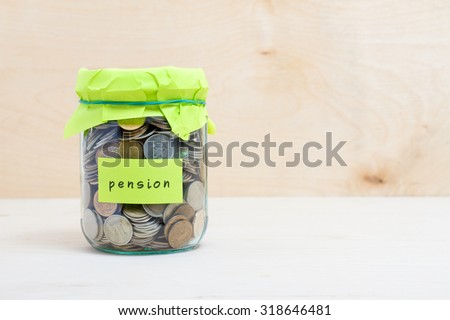 Financial concept. Coins in glass money jar with pension label. Wooden background - stock photo