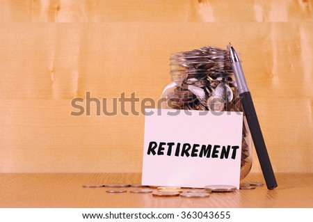 Financial concept. Coins in glass money jar with retirement label. Wooden background - stock photo