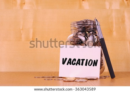 Financial concept. Coins in glass money jar with vacation label. Wooden background - stock photo