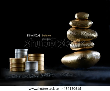 Financial concept image representing investment balance. Gold and silver currency coins with stacked stones against black with generous accommodation for copy space.