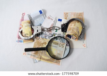 Financial Concept Loupe, Handcuffs and Money on a White Background - stock photo