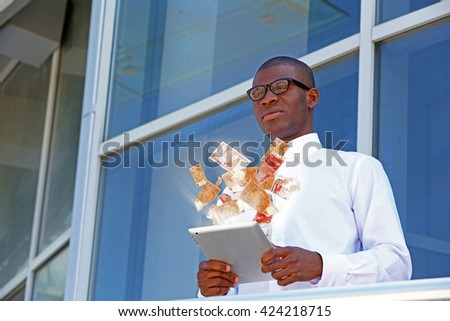 Financial concept. Make money on the Internet. Handsome African American businessman with digital tablet near business centre - stock photo