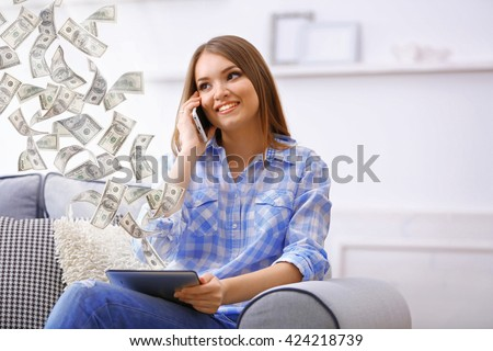 Financial concept. Make money on the Internet. Pretty woman talking on cell and holding tablet computer - stock photo