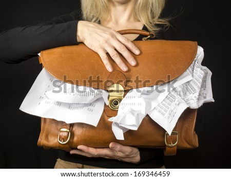Financial concept photo showing a closeup of a female executive holding a briefcase overflowing with paperwork.