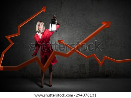 Financial concept with young pretty businesswoman with lantern in darkness