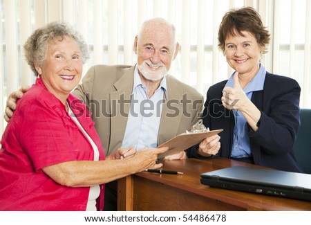 Financial consultant gives thumbs up as she advises retired couple. - stock photo