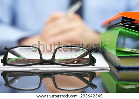 financial consultant in background with eyeglasses  in front with growing arrows, business and success concept - stock photo