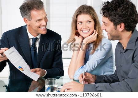 Financial consultant presenting a business investment to a smiling young couple - stock photo