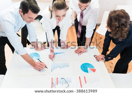 Financial consultants in bank analyzing data and discussing graphs - stock photo