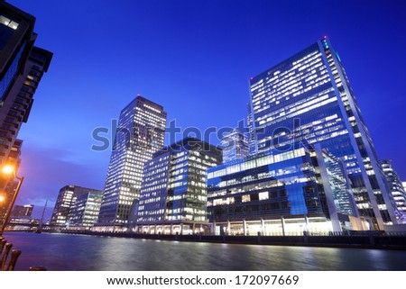Financial Corporate Skyscraper office building at night in Canary Wharf, London City, England, UK  - stock photo