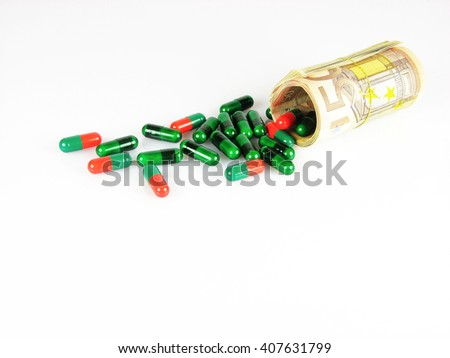 Financial cost of healthcare concept with assorted pharmaceutical capsules and medication spilling from a roll of 50 euro banknotes over a white background with copy space - stock photo