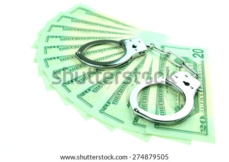 Financial crime concept with handcuffs on money background