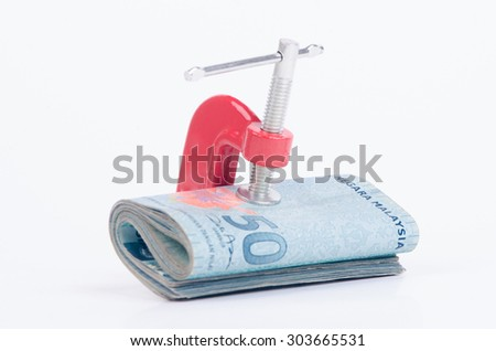 Financial crisis/Business concept with money and clamp - stock photo