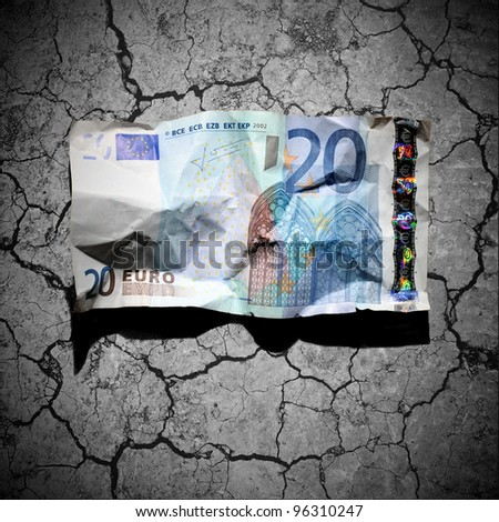 Financial crisis concept - crumpled 20 euro banknote on dry soil background - stock photo