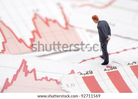 Financial crisis. Figure of businessman on financial charts - stock photo
