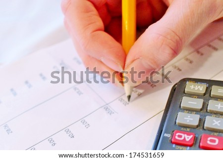 Financial data analyzing accounting with pencil and calculator - stock photo