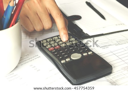 Financial data analyzing. Close-up photo of a businessman's hand counting on calculator in office. Soft focus