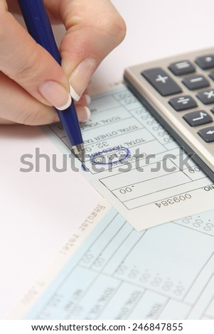 Financial data analyzing. Counting on calculator. A hand with a blue pen - stock photo