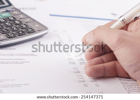 Financial data analyzing. Counting on calculator. Close-up. - stock photo
