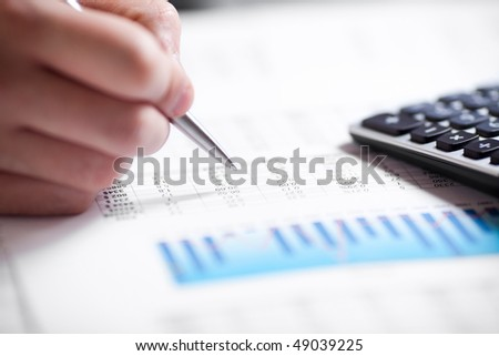 Financial data analyzing. Counting on calculator. Close-up. Selective focus - stock photo
