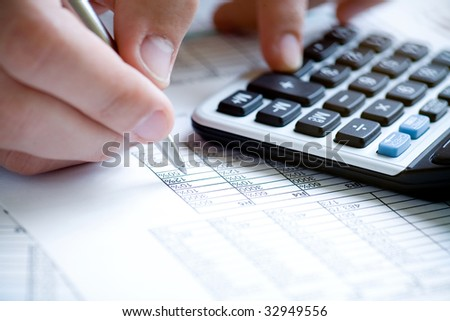 Financial data analyzing. Counting on calculator. Hand with pen on calculator. - stock photo