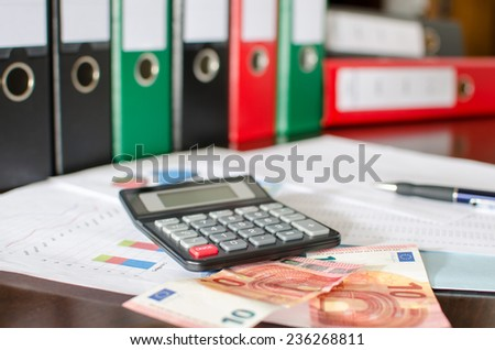 Financial documents with calculator and banknotes - stock photo