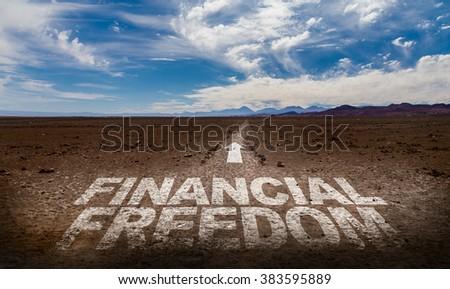 Financial Freedom written on desert road - stock photo