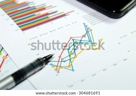 Financial graphs analysis and pen. - stock photo