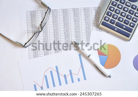 Financial graphs and business report with a calculator, glasses and pen on a table - stock photo