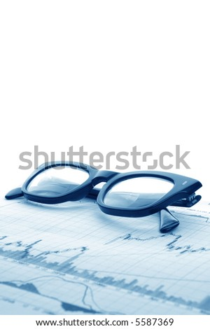 Financial graphs with some serious specs for looking them over. - stock photo