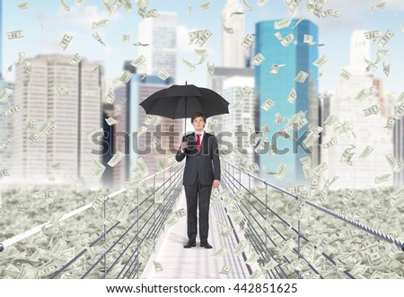 Financial growth and success concept with businessman holding umbrella and standing in the middle of bridge with abstract dollar banknote rain on New York city background - stock photo