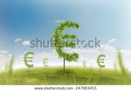 Financial growth and success on a green summer natural green grass landscape with a single trees in the shape of a money sign showing a business concept of growing prosperity and investments. - stock photo