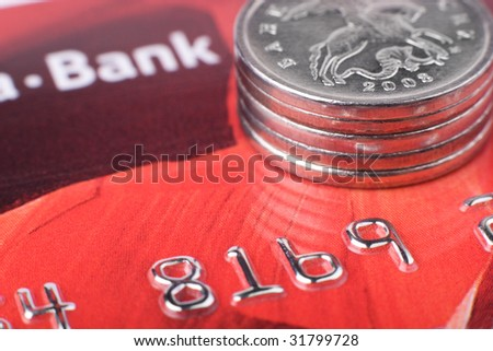 Financial issues: macro of coins stack on credit card. Focus on coin edge