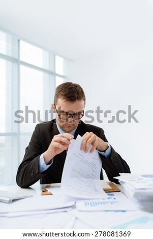 Financial manager reading contract at his table - stock photo