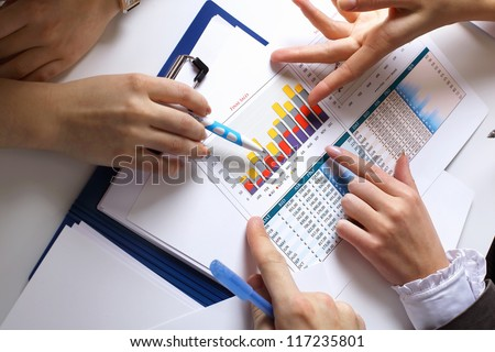 Financial paper charts and graphs on the table - stock photo