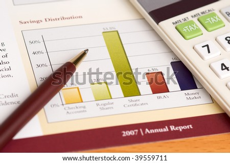 Financial Planning and Review of Year End Reports with Pen and Calculator on wood desktop. - stock photo