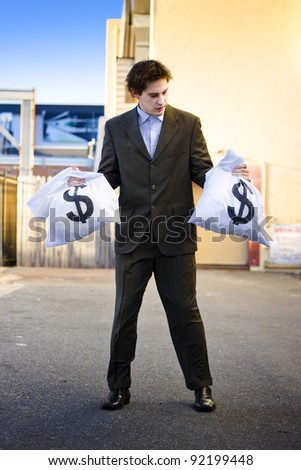 Financial Planning Concept With An Unsure Business Man Looking For Help And Advice On Where To Invest His Bags Of Money Wealth And Profit - stock photo