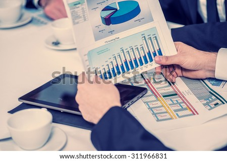 Financial Report. Confident businessman sitting at the table at a business meeting in the office and keep the documents in the hands - stock photo