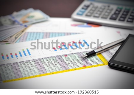 financial report on table with money, pen and phone